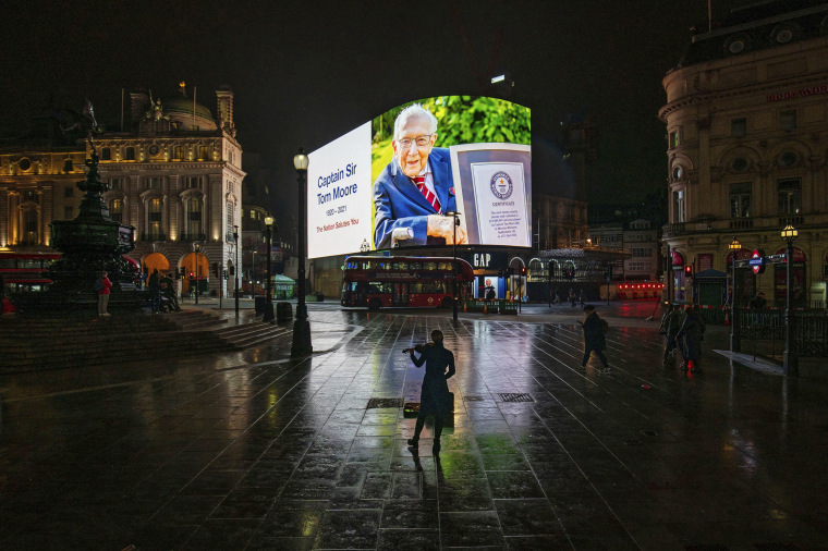 A woman plays the violin as a tribute to Captain Sir Tom Moore in Piccadilly Circus, London, on Feb 2, 2021.