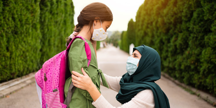 Young Muslim woman putting a protective mask on her daughter's face outdoor.
