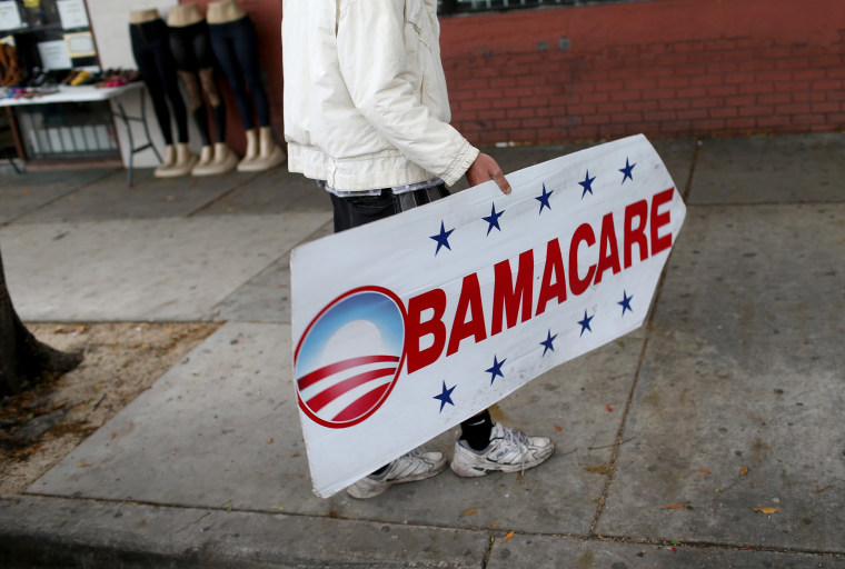 Image: Pedro Rojas holds a sign directing people to an insurance company where they can sign up for the Affordable Care Act, also known as Obamacare