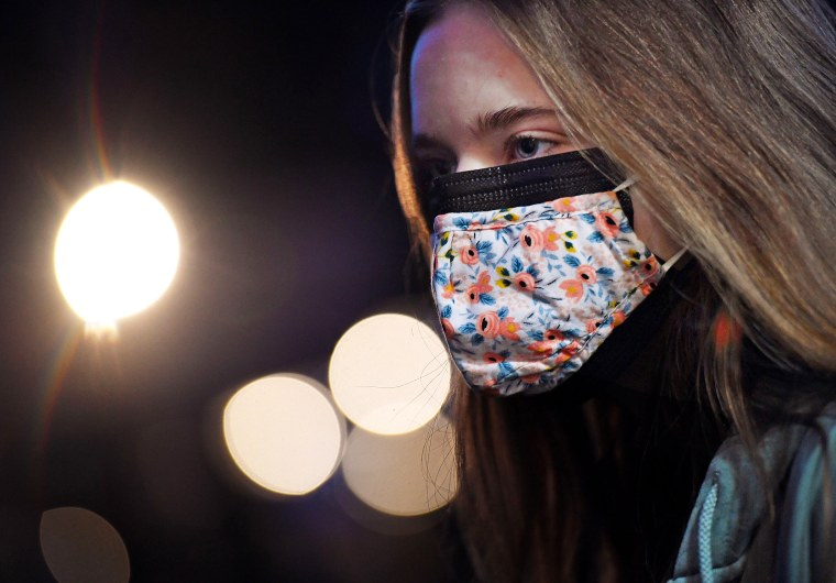 A woman wearing two facemasks, a cloth mask over a surgical mask, in Arlington, Va., on Fe. 8, 2021.