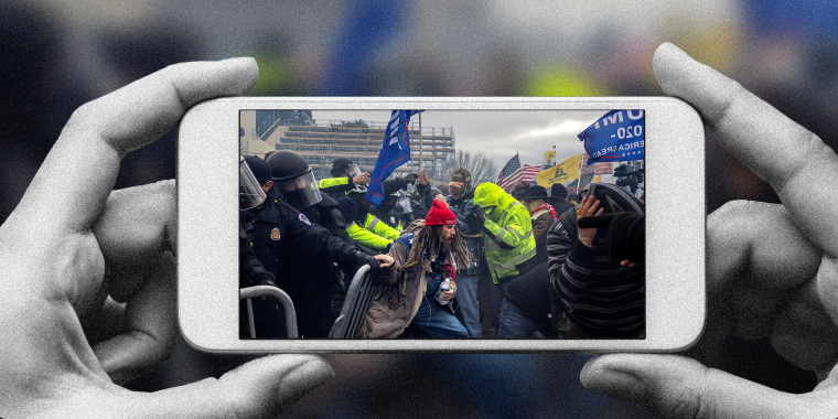 Photo illustration of a hands holding a phone with the image of Trump supporters clashing with the police and security forces as people try to storm the US Capitol.