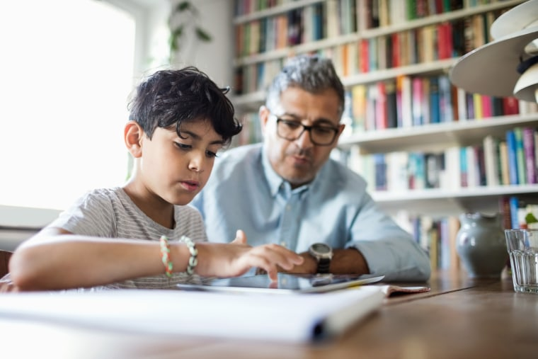 Father assisting son in using digital tablet while studying at brightly lit home