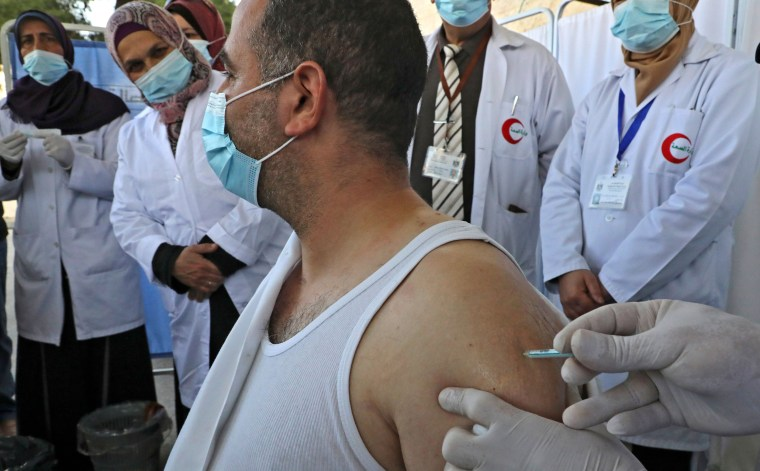 Image: A Palestinian health worker gets vaccinated against COVID-19.