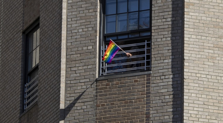 A rainbow flag is waved through window grills in an apartment overlooking the LGBTQ Pride march on June 30, 2019, in New York.