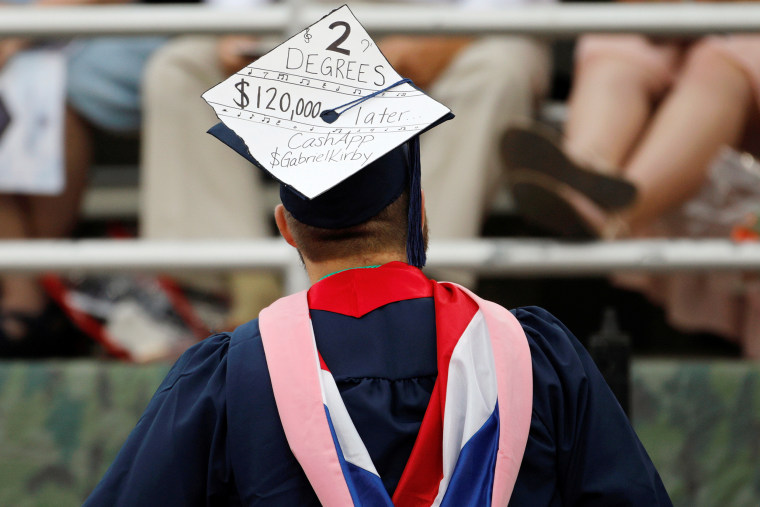 A graduate wears a mortar board adorned with a message about the cost of his education before the start of commencement exercises at Liberty University in Lynchburg, Virginia