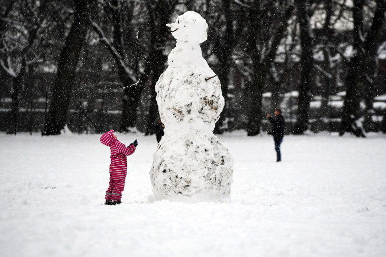 Image: A child looks at a giant snowman as they stand in a snow-covered Victoria Park in Glasgow on Feb. 9, 2021. Cold weather swept across northern Europe bring snow and ice.