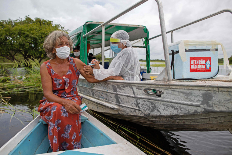 Olga D'arc Pimentel, 72, is vaccinated by a health worker with a dose of Oxford-AstraZeneca COVID-19 vaccine in the Nossa Senhora Livramento community on the banks of the Rio Negro near Manaus, Amazonas state, Brazil on Feb.  9, 2021.