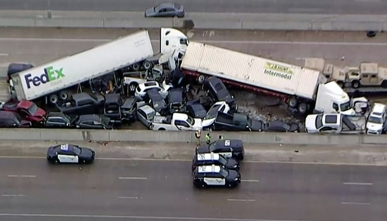 Image: Cars and trucks are wedged together after a morning crash on the ice covered I-35 in Fort Worth