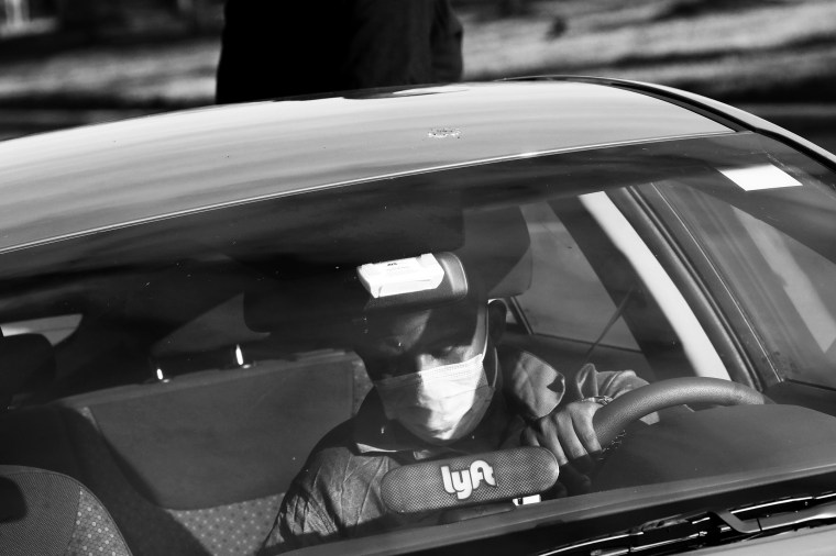 Image: A Lyft rideshare driver wears a mask in Washington
