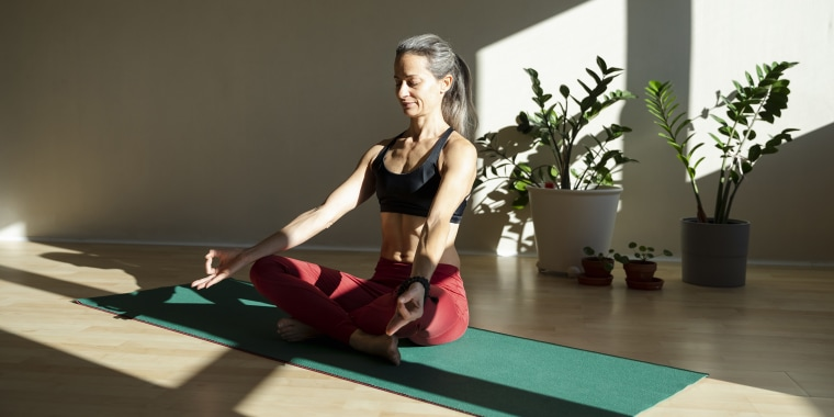 Yogini meditating on exercise mat in living room on sunny day