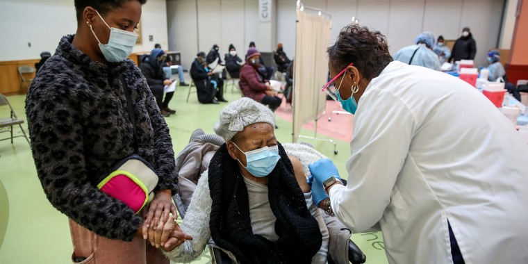 Juanta J. Gordon gets a Moderna coronavirus vaccination shot from her daughter, nurse Zyra D. Gordon Smith, at Trinity United Church of Christ in Chicago on Saturday.
