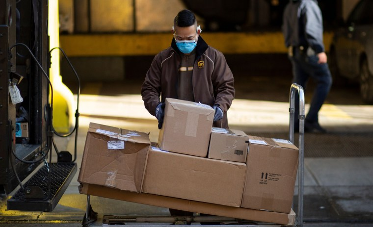 Image: A UPS worker organizes boxes to be delivered in midtown New York