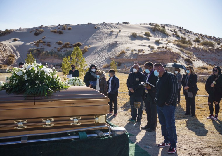 Image: Family and friends attend the funeral of Humberto Rosales, who died from Covid-19 complications, at Memorial Pines Cemetery in Santa Teresa, N.M.