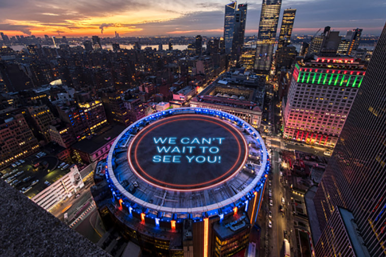 """A sign that reads, """"We can't wait to see you!"""" lights up the top of Madison Square Garden."""