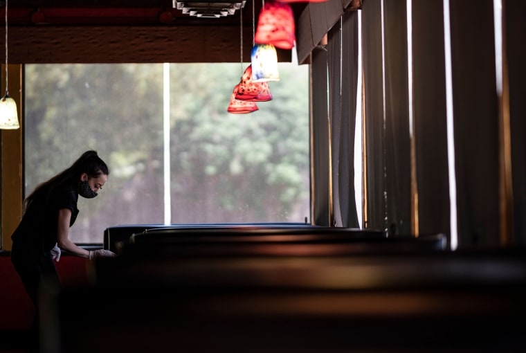 Image: Waitress disinfects a table in a restaurant in Oklahoma