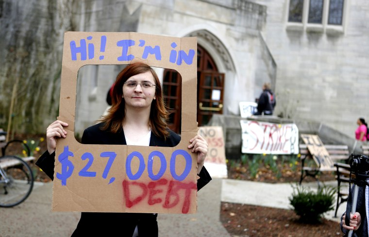 Indiana University senior Randall Burns holds a sign he said represents the average debt a college student has after graduating, during the IU Strike protest on April 11, 2013 in Bloomington, Ind.
