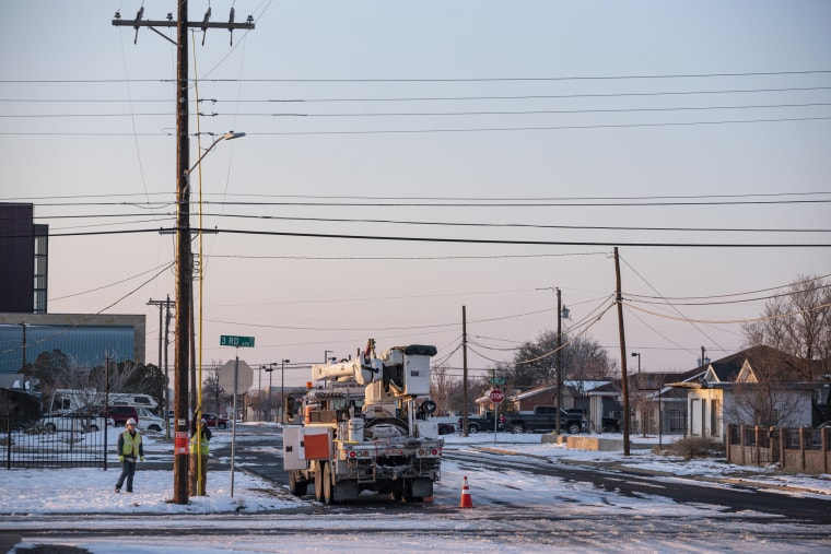 Image: An Oncor Electric Delivery crew works on restoring power to a neighborhood following the winter storm that passed through Texas Feb. 18, 2021, in Odessa, Texas.