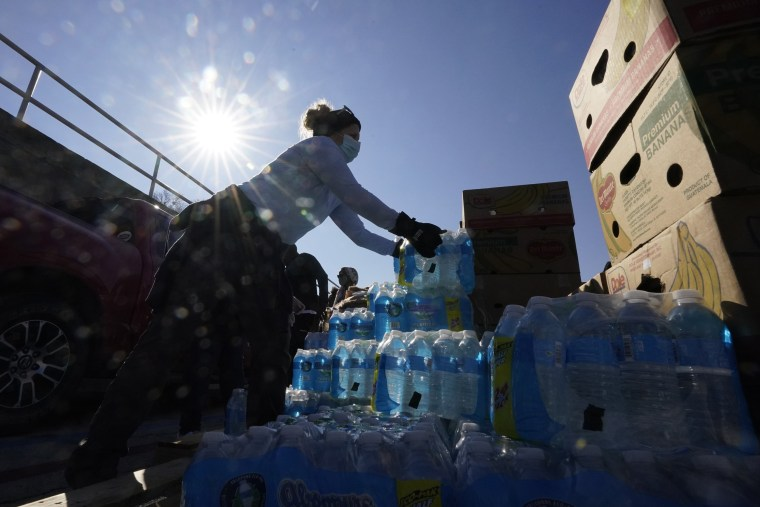 Image: Volunteers load water for people at a San Antonio Food Bank drive-through food distribution site