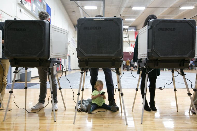 Image: A child waits between her father's legs as he and other voters cast their ballots for the mid-term elections
