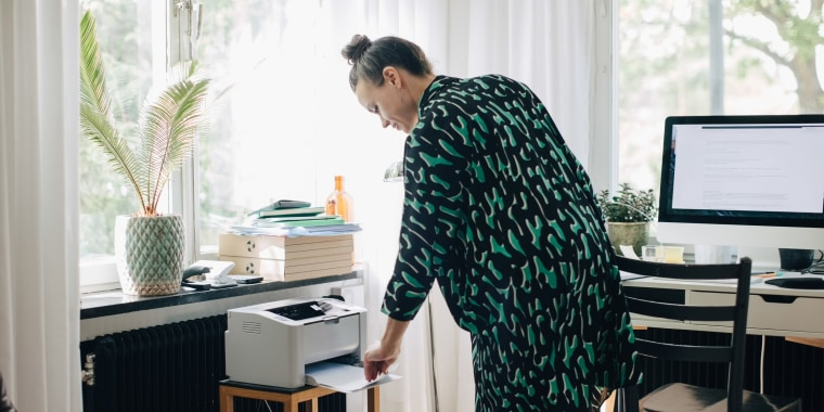 Young businesswoman using computer printer at home office