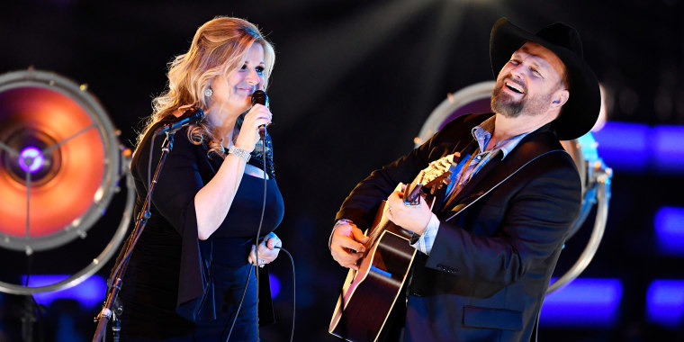 Garth Brooks and Trisha Yearwood smilingly sing onstage against a dark background