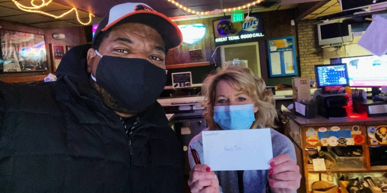 """T.J. Smith presents a """"Famous Fund"""" check to a Baltimore restaurant owner."""