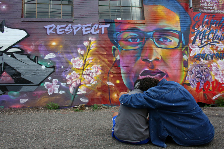 People visit a mural ahead of the first anniversary of Elijah McClain's death