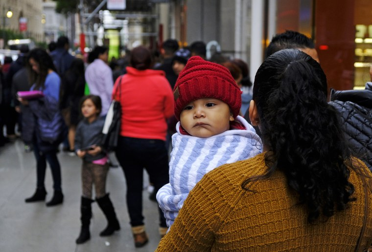 A woman holds a child in a line snaking around the block outside a U.S. immigration office on Jan. 31, 2019, in San Francisco.