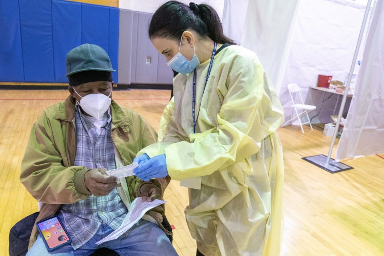 Image: Registered Nurse Rita Alba points out to Beltran Orlando the return date on his vaccination card while he rests in the recovery area after receiving the first dose of coronavirus vaccine at a vaccination site in Bronx, N.Y., on Jan. 31, 2021.