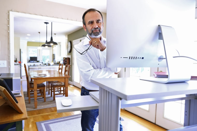 Businessman Works At Standing Computer Desk At Home. These are the best standing desks according to ergonomic experts. Shop the best standing desks of 2021 to complete your work from home setup.