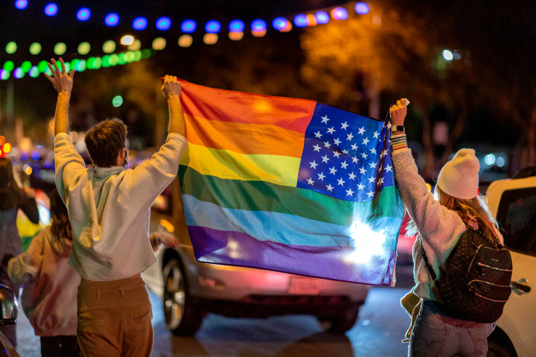 People wave a rainbow flag as they celebrate the presidential election in West Hollywood, Calif., on Nov. 7, 2020.