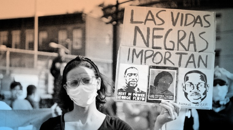 """Image: An activist holds a sign that reads \""""Las vigas Negras importan\"""" at a Black Lives Matter protest in June 2020."""