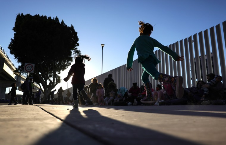 Image: Children play as people who are seeking asylum in the United States are gathered outside the El Chaparral border crossing on Feb. 19, 2021 in Tijuana, Mexico.