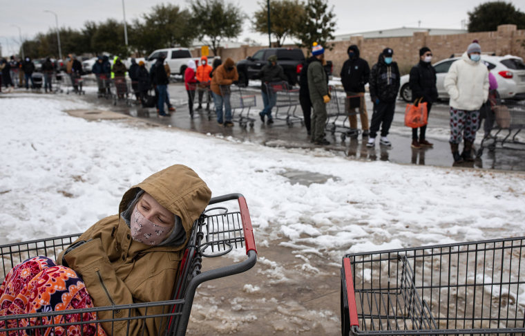 Image: A girl sits in a shopping cart waiting in a long line to enter a grocery store in Austin, Texas.