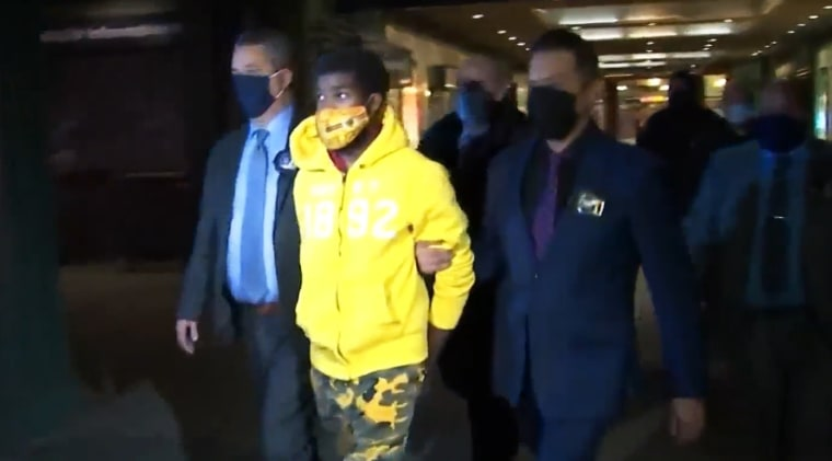 Police lead Khari Covington away from the NYPD station in the Coney Island subway station on Jan. 6, 2021, in Brooklyn.
