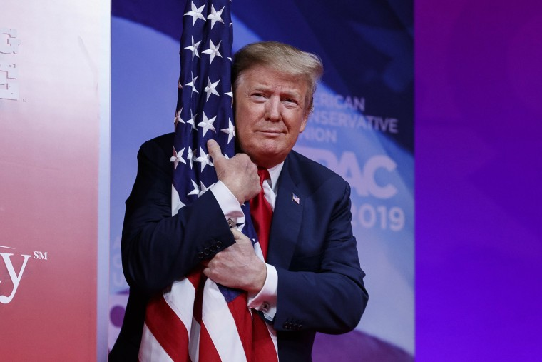 Image: President Donald Trump hugs the American flag as he arrives to speak at the Conservative Political Action Conference, CPAC 2019