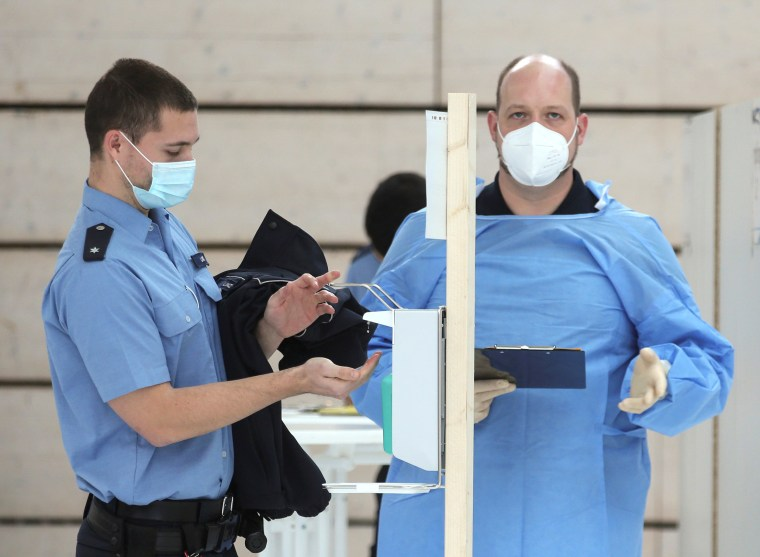 Image: A German police staff member disinfects his hands to receive a dose of AstraZeneca's vaccine against the coronavirus disease (COVID-19) during a vaccination program, in Mainz, Germany