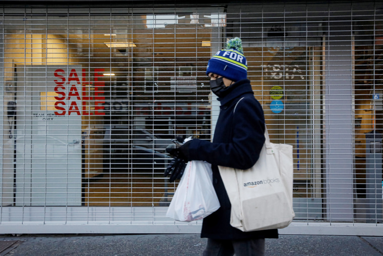 Image: A shopper passes by a retail store that was recently closed in Brooklyn, New York