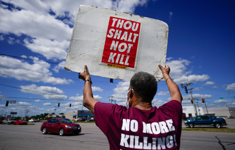 """Image: Back of a person holding up a sign that reads,""""Thou shalt not kill"""" and the back of their shirt reads,""""No more killing""""."""