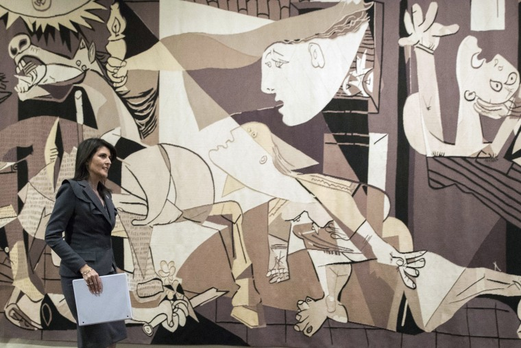"""Image: United States Ambassador to the United Nations Nikki Haley walks past a tapestry woven by Atelier J. de la Baume-Durrbach of Pablo Picasso's """"Guernica"""" as she arrives to speak to reporters at United Nations headquarters."""