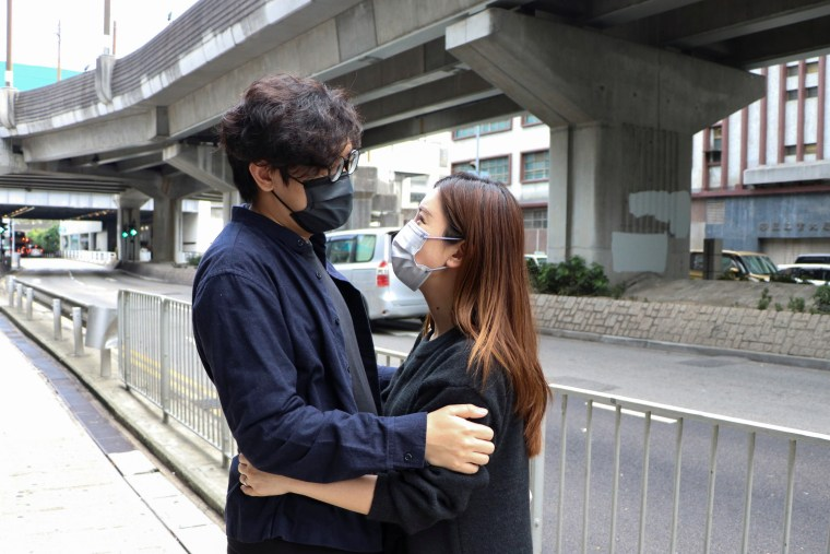 Image: Pro-democracy activist Sam Cheung hugs his wife before reporting to the police station over national security law charges, in Hong Kong
