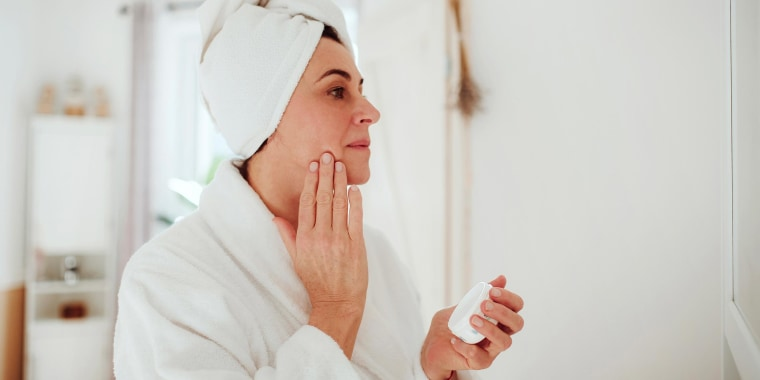 Woman rubbing lotion on her face in a bathrobe, from Dermstore