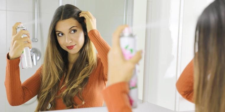 Woman using dry shampoo on her hair