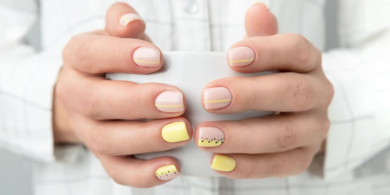 Woman with trendy manicure design holding a coffee mug