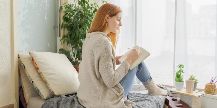 Woman bullet journaling in her bedroom