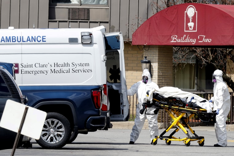 Image: Healthcare officials prepare to load a patient into an ambulance at Andover Subacute and Rehab Center in Andover, New Jersey
