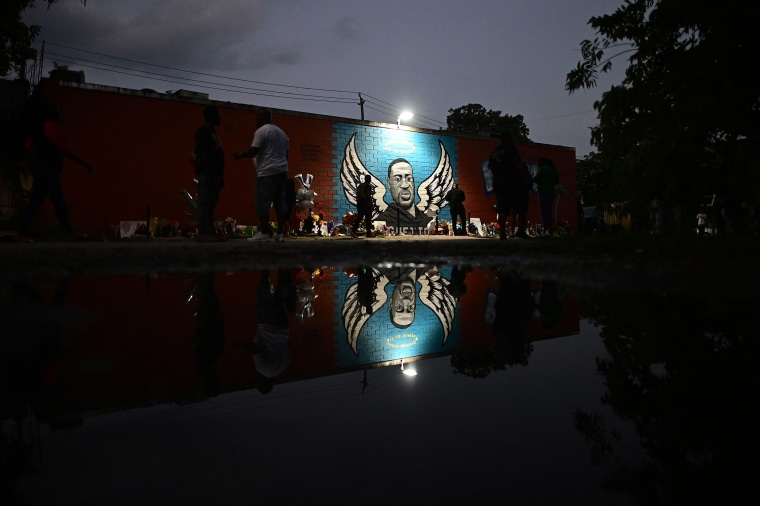 Image: People stand in front of a mural of George Floyd in Houston, Texas