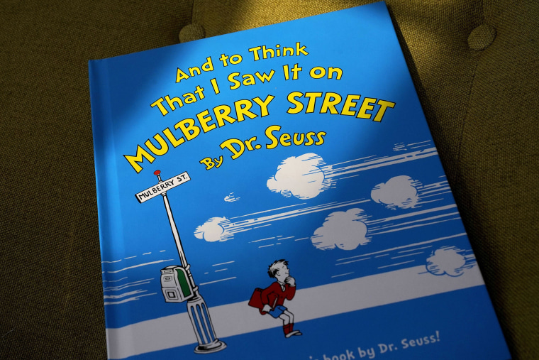 """Image: A copy of the book \""""And to Think That I Saw It on Mulberry Street,\"""" by Dr. Seuss, rests in a chair,"""