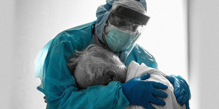 Image: A doctor hugs and comforts a patient in the hospital
