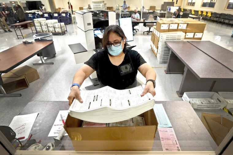 Image: An election official counts ballots inside the Maricopa County Recorder's Office in Phoenix